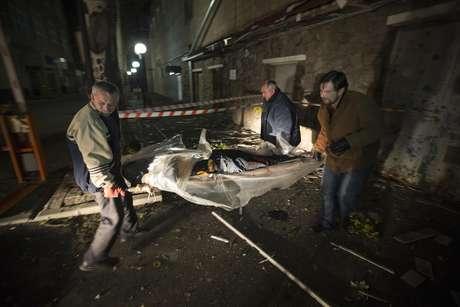 Homens retiram corpo de vítima da Cruz Vermelha que morreu na Ucrânia nesta quinta-feira