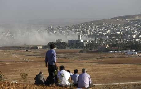 <p>Curdos turcos observam a cidade s&iacute;ria curda de Kobani do topo de uma colina perto da fronteira entre Turquia e S&iacute;ria, na regi&atilde;o do port&atilde;o de Mursitpinar, em 10 de outubro</p>