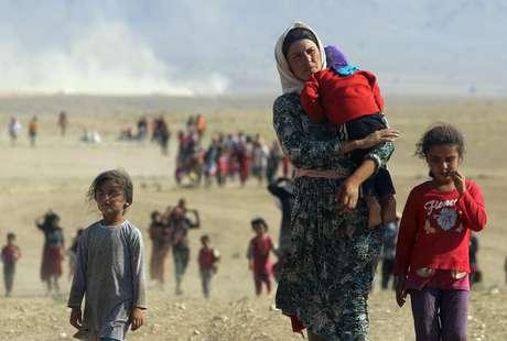 Mulheres e crianças yazidis caminham para fronteira do Iraque