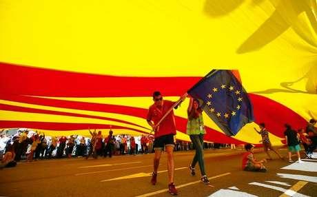 <p>Manifestantes carregam&nbsp;bandeira da Uni&atilde;o Europeia sob uma bandeira gigante da Catalunha durante protesto em Barcelona, no Dia Nacional da Espanha</p>