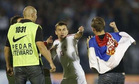 Burim Kukeli, da seleção da Albânia, e um colega de time brigam com um torcedor da Sérvia durante partida entre as seleções dos dois países pelas eliminatórias da Eurocopa de 2016. 14/10/2014.