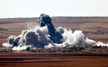 <p>Fumaça é vista em vila nos arredores da cidade síria de Kobani nesta quarta-feira</p>