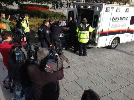 Soldado ferido a tiros perto do Parlamento do Canadá é movido para dentro de uma ambulância por policiais e médicos