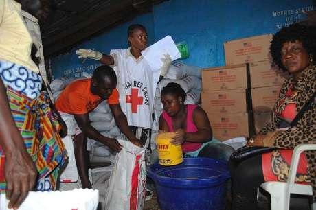 <p>Trabalhadores da Cruz Vermelha distribuem alimentos em Monróvia, na Libéria, um dos países mais afetados pelo surto de Ebola na África Ocidental</p>