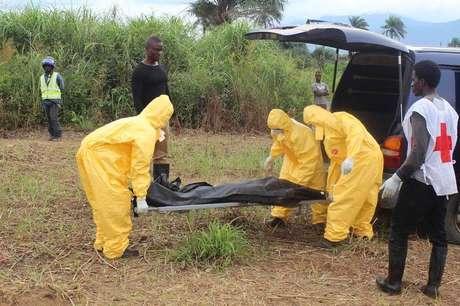<p>Funcionários de serviços de saúde carregam corpo de vítima com ebola no distrito de Waterloo, Freetown (Serra Leoa)</p>