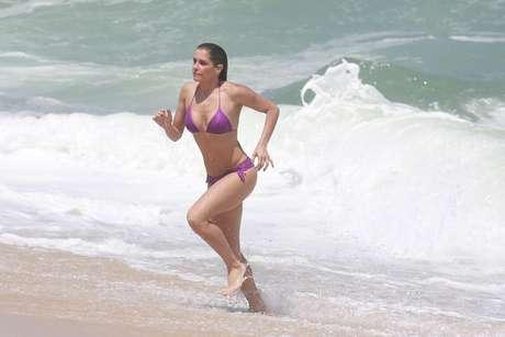 Deborah Secco e Rodrigo Simas trocaram vários beijos nesta quinta-feira (23) durante a gravação da novela Boogie Oogie, da trama das 18h, na praia da Macumba, no Rio de Janeiro. A atriz esbanjou sua boa forma ao exibir o biquíni que vestia quando entrou no mar.