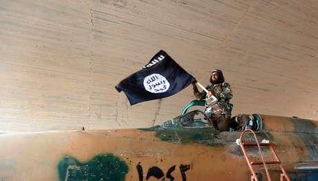 <p>Combatente do Estado Islâmico ergue uma bandeira da organização terrorista emcima de um caça, emagosto deste ano</p><p></p>