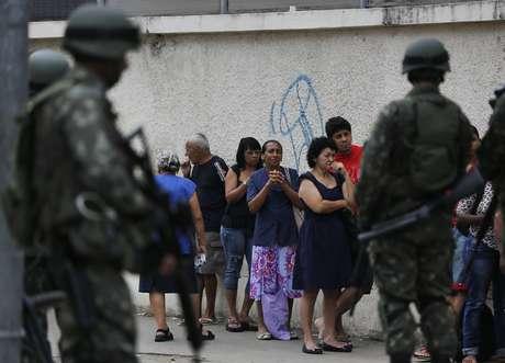Soldados fazem a segurança em porta de colégio no Complexo da Maré, Rio de Janeiro