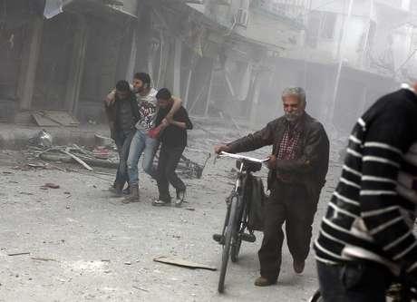 <p>Um homem é socorrido após um ataque aéreo realizadopor forças do regime sírio na cidade de Douma, a nordeste da capital Damasco, um reduto da oposição desde o início da revolta contra o presidente Bashar al-Assad, em 13 de abril de 2014</p>