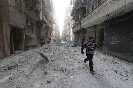 <p>Homem corre num local atingido por um suposto ataque de forças leais ao presidente sírio, Bashar al-Assad, num bairro de Aleppo, na Síria</p>