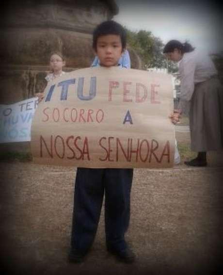 Menino leva cartaz na reza pela água em Itu