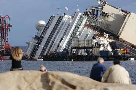Pessoas olham navio de cruzeiro Costa Concordia tombado na costa da Toscana, na Itália