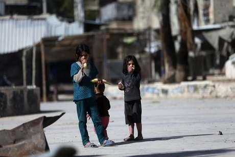 Crianças sírias comem milho em uma rua em Douma, no leste da al-Ghouta, perto de Damasco; o EI fechou escolas ao leste do país nesta sexta