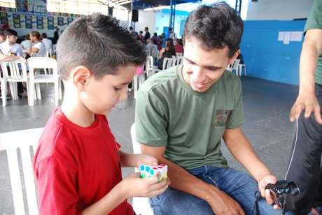 O professor Caio Ferraro observa aluno treinando a montagem do cubo