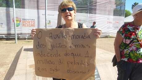 Eliane Lima carrega cartaz que relaciona obscenidade com benefícios do judiciário