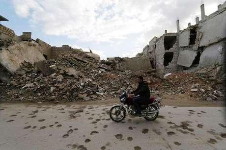 Homem conduz sua motocicleta em frente a escombros de prédios em Maaret al-Naaman, na província de Idlib, Síria. 27/11/2014.