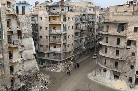<p>Pessoas caminham em bairro da cidade síria de Aleppo em 10 de dezembro</p>