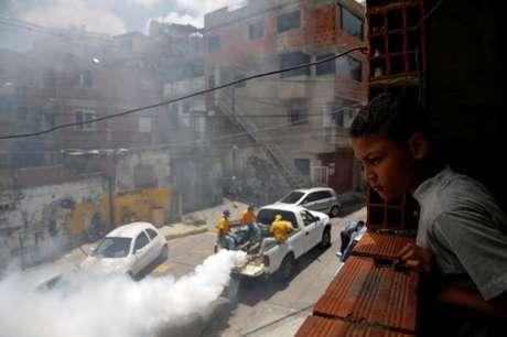 Menino observa trabalhadores aplicando remédio contra mosquito da dengue em rua de Caracas. 22/09/2014