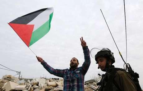 Manifestante palestino discute com soldados israelenses durante protesto contra assentamentos judaicos perto de Ramallah, na Cisjordânia, no início de dezembro. 10/12/2014
