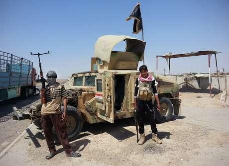 Integrantes do Estado Islâmico ficam em frente a armamento conquistado no Iraque
