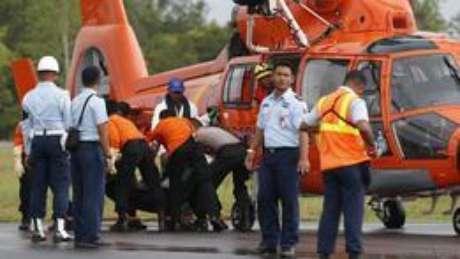 Equipe transporta corpo de passageiro do voo QZ8501 (foto: Reuters)