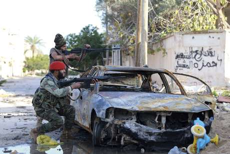 Forças pró-governo da Líbia miram suas armas durante confrontos com os revolucionários líbios, uma aliança formada por  antigos rebeldes anti-Kaddafi, em Benghazi, em 28 de dezembro