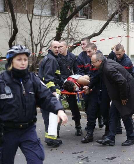 <p>Bombeiros levam vítima em maca após ataque a jornal satírico em Paris, em 7 de janeiro</p>