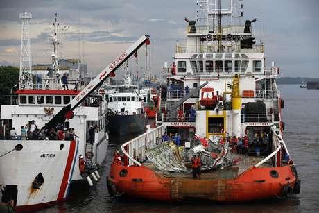 Equipes de resgate transportam a cauda da aeronave da AirAsia após ela ser resgatada do Mar de Java, em 10 de janeiro