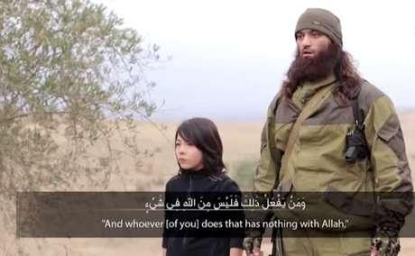 O menino aparece do lado de um jihadista adulto que fala por alguns segundos