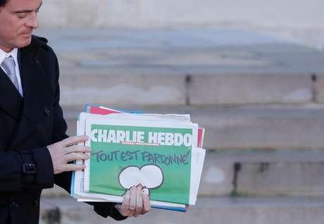 Primeiro-ministro francês Manuel Valls segura uma cópia do semanário Charlie Hebdo ao deixar encontro do gabinete em Paris.  14/01/ 2015.