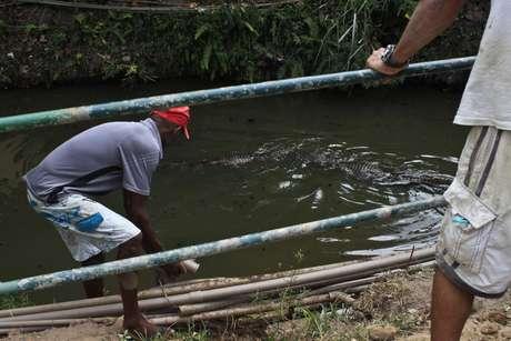 <p>Moradores se arriscam para pegar água de bica no Canal das Taxas, onde vivem jacarés</p>