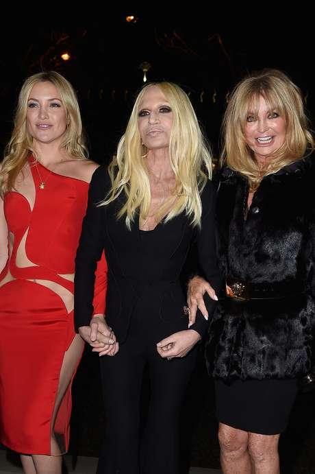 <p>A atriz Kate Hudson usou vestido mostrado da passarela e posou ao lado da m&atilde;e, a atriz Goldie Hawn, e da diretora da marca, Donatella Versace</p>