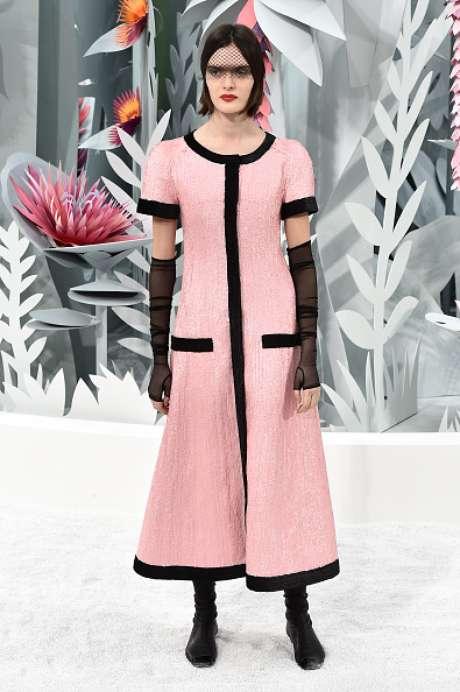 O tradicional casaquinho do tailleur Chanel se alonga e vira um vestido casaco rosa com debrum preto