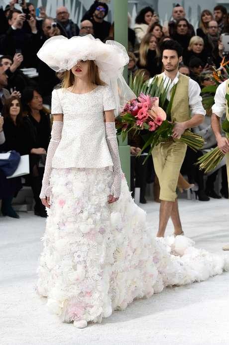 O vestido de noiva proposto por Karl Lagerfeld para Chanel trás saia com cauda, blusa com cristais, luvas e chapéu de tule no lugar do véu
