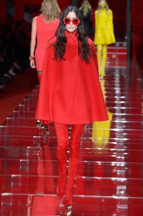 <p>Casaco tipo pelerine, lembrando os anos 60, é a proposta da Versace, também em tom vermelho</p>