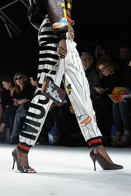 """<p class=""""text"""">O logotipo da calça esportiva da Moschino se mistura a outros desenhos infantis no look, inclusive o coelho Pernalonga estampado na bolsa</p><p class=""""text""""></p>"""