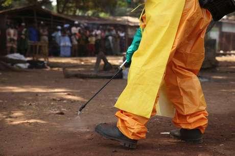 <p>Integrante da Cruz Vermelha desinfeta local onde havia pessoa com suspeita de Ebola</p>