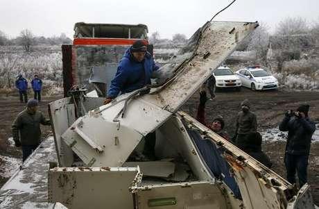 Trabalhadores locais transportam destroços do voo MH17 no local da queda do avião, perto do vilarejo de Hrabove, no leste da Ucrânia, no ano passado. 16/12/2014