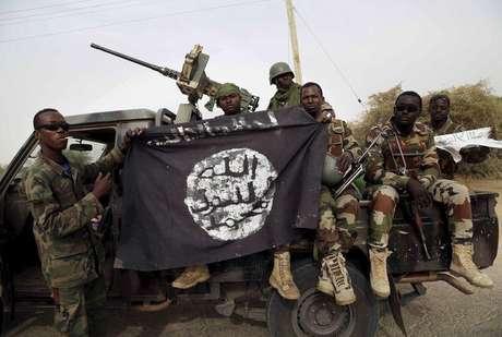 Soldados do Níger segurando bandeira do grupo derrotado, Boko Haram, após retomar a cidade de Damasak, na Nigéria.  19/03/2015
