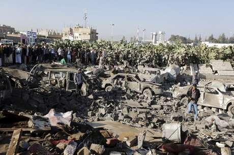 Pessoas cercam área alvo de um ataque aéreo nos arredores do aeroporto de Sanaa