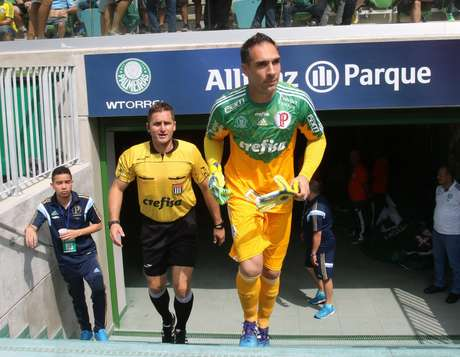 <p>Palmeirense Fernando Prass e árbitroMarcelo Rogério entram em campo com camisas patrocinadas pela Crefisa: fim da parceria com a FPF após recomendação da Fifa</p>