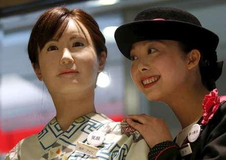 Uma atendente da loja de departamento japonesa Nihonbashi Mitsukoshi posa ao lado do robô humanoide Aiko Chihira, desenvolvido pela Toshiba, em Tóquio  20/042015.