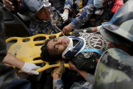Pemba Lama, de 15 anos, é levado a uma ambulância após ser resgatado de escombros cinco dias depois do terremoto que atingiu Katmandu