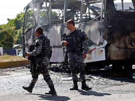 Policías estatales examinan los restos de un autobús que fue incendiado en Guadalajara, México, como parte de los bloqueos que una organización criminal provocó en la ciudad el 1 de mayo de 2015, el 2 de mayo de 2015.