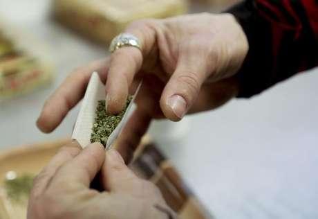 Usuário de maconha prepara cigarro em Seattle.