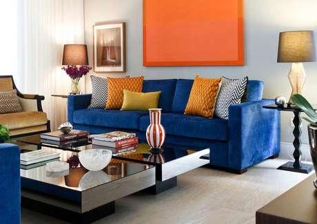 Montada com combinação de azul e cores quentes, esta sala inclui detalhes naturais e objetos decorativos modernos