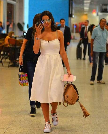 Bruna Marquezine embarca com vestido branco, tênis, bolsa bege e óculos: look fresco e jovem