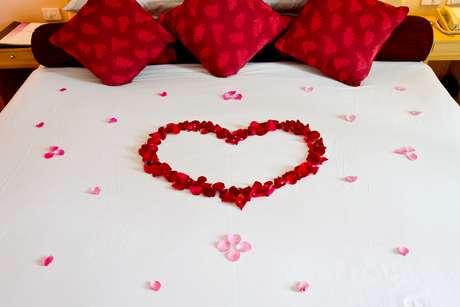 No quarto, a decoração deve ser romântica. Por isso, experimente colocar na cama algumas almofadas e colcha de cor vermelha