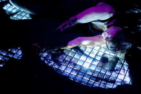 Juliana Moraes dança sobre superfície coberta de borracha triturada fazendo vazar luz com seus movimentos