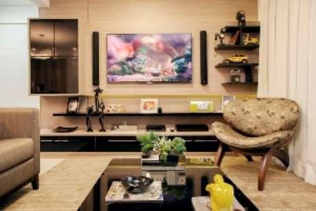 Manter sobriedade dos tons dos móveis no sofá e apostar em cores nos acessórios é uma saída certeira para colorir a sala sem exagerar